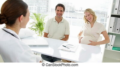Doctor talking with expectant parents in office at the...