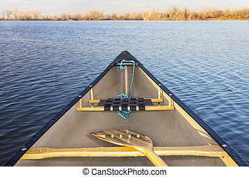 canoe bow on lake - canoe bow with a wooden paddle on a calm...