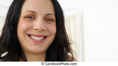 Brunette pregnant woman smiling at camera at the hospital