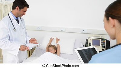 Sick little girl lying in bed talking to nurse and doctor at...