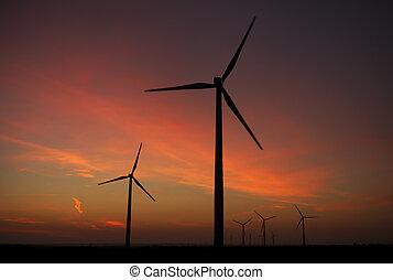 Sunrise over wind farm - The sun rises above the turbines of...