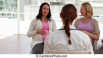 Pregnant women talking together at antenatal class at the...