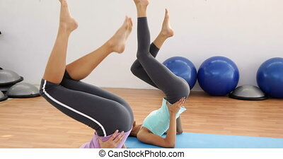 Fit women doing pilates together in studio at the gym