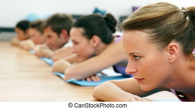Fitness class lying on mats smiling at camera at the gym