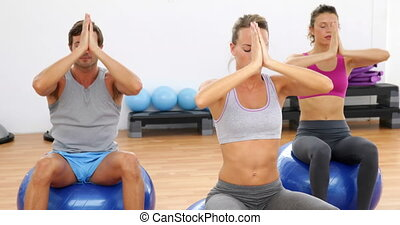 Fitness class sitting on exercise balls