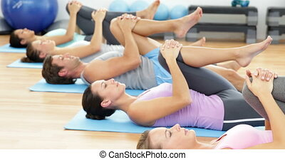 Pilates class lying on mats stretching at the gym