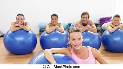 Fitness class leaning on exercise balls smiling at camera at...