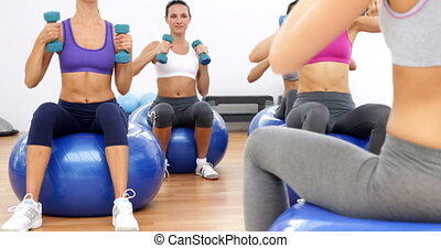 Fitness class sitting on exercise balls lifting hand weights...