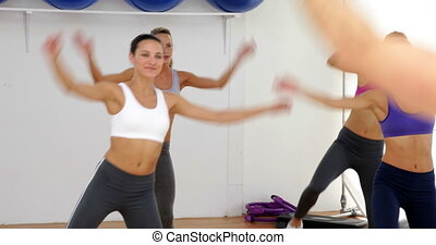 Aerobics instructor leading a happy class of women at the...