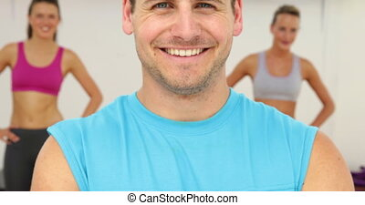 Aerobics instructor smiling at camera at the gym