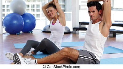 Couple stretching arms together on exercise mat at the gym