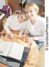 Mother with Teenage Daughter Making Origami Crafts Indoors...