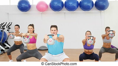 Kettle bells instructor leading a happy class of women at...