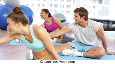 Fitness class sitting together and stretching at the gym