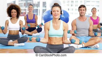 Fitness class sitting together and lifting dumbbells at the...