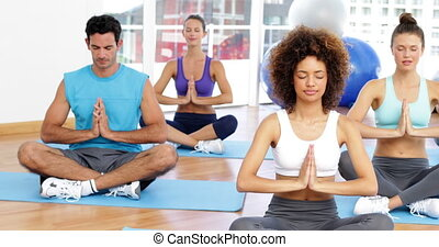 Yoga class sitting in lotus pose together at the gym