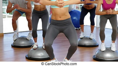 Fitness class squatting on bosu balls at the gym