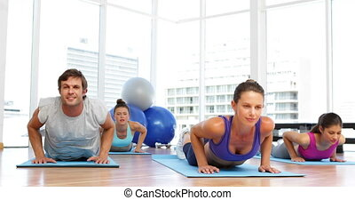 Yoga class doing cobra pose together on exercise mats at the...