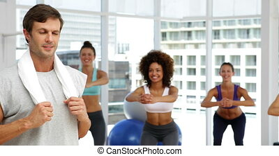 Fitness class squatting on bosu balls while instructor...
