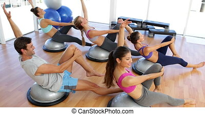 Fitness class lying on bosu balls t