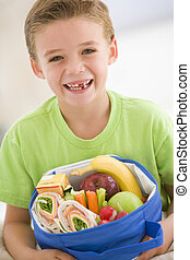 Young boy holding packed lunch in living room smiling