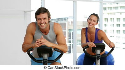 Fit couple exercising on bikes in fitness studio at the gym