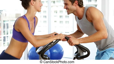 Fit couple exercising on bikes in f