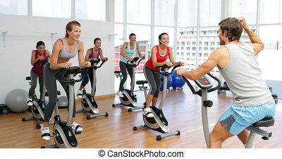 Spinning class in fitness studio led by energetic instructor...