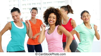Pretty instructor leading zumba class in fitness studio at...
