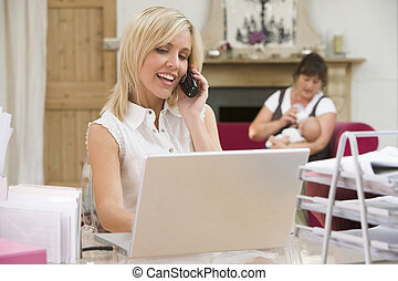 Woman in home office with laptop and telephone with mother...