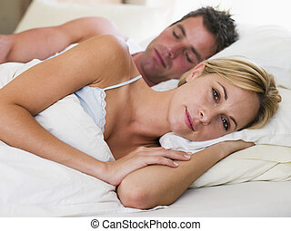 Couple lying in bed with the man sleeping - man asleep and...