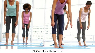 Yoga class warming up in fitness studio at the gym