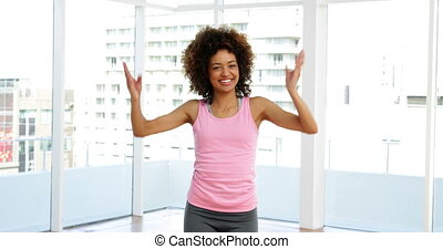 Pretty instructor doing zumba in fitness studio at the gym