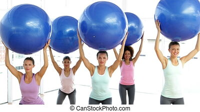 Fitness class in studio lifting exercise balls while...