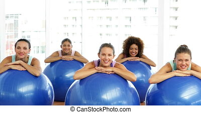 Fitness class in studio leaning on exercise balls smiling