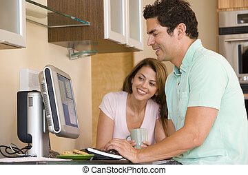 Couple in kitchen with computer and coffee smiling