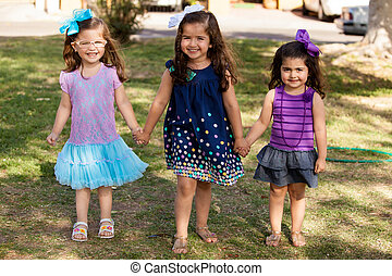 Cute cousins holding hands - Full length portrait of a group...