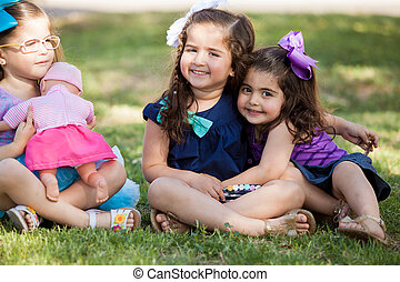 Little sisters handing out at a park - Portrait of three...