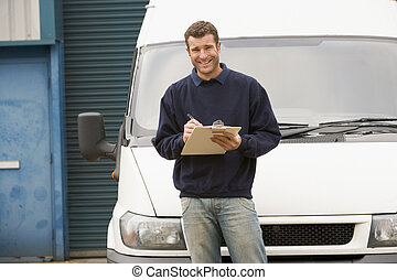 Deliveryperson standing with van writing in clipboard...