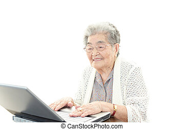 Smiling old woman - Old woman enjoys computer