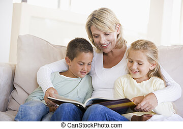 Woman and two children sitting in living room reading book...