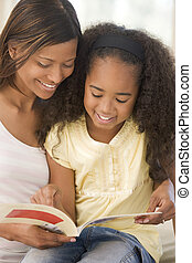 Woman and young girl sitting in living room reading book and...