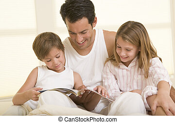 Man with two young children sitting in bed reading a book...