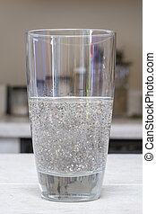 Chia seed beverage - Closeup of tall glass beverage half...
