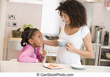 Woman and young girl in kitchen with cookies and coffee...
