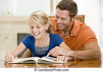 Man and young girl reading book in dining room smiling