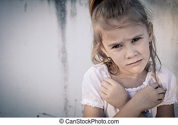 Portrait of sad little girl sitting near wall in the day...