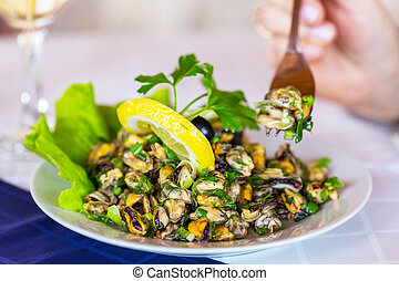 fresh grilled mussels with herbs and lemon on white plate,...