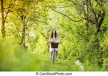 Young woman with bike - Pretty young woman riding retro bike...
