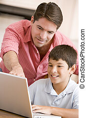 Man helping young boy in kitchen with laptop smiling